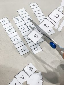 Using scissors to cut out the individual lowercase letters