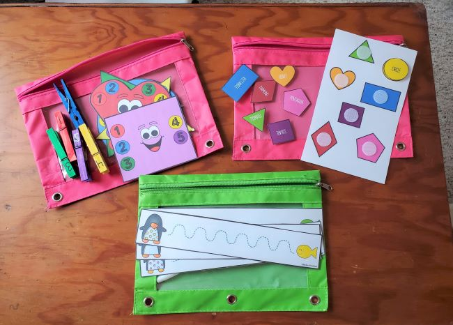 Image of three busy bags. shapes with clothespins, shape matching, and penguin tracing.