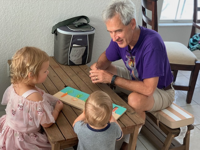 kids playing with lovevery puzzle with papa